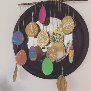 Cardboard egg shapes decorated and hung