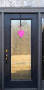 A photo of a door with a paper heart pinned on the front