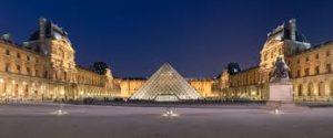 A night-time view of the Louvre Museum in Paris