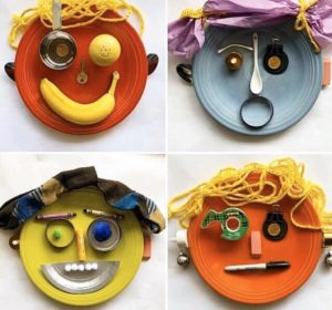 4 plates with faces made on them using a variety of found objects